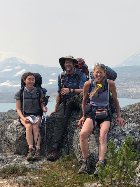Photo of Annie, Pete and Sara Hagen sitting on large rocks on top of a ridge with water and mountains behind them.