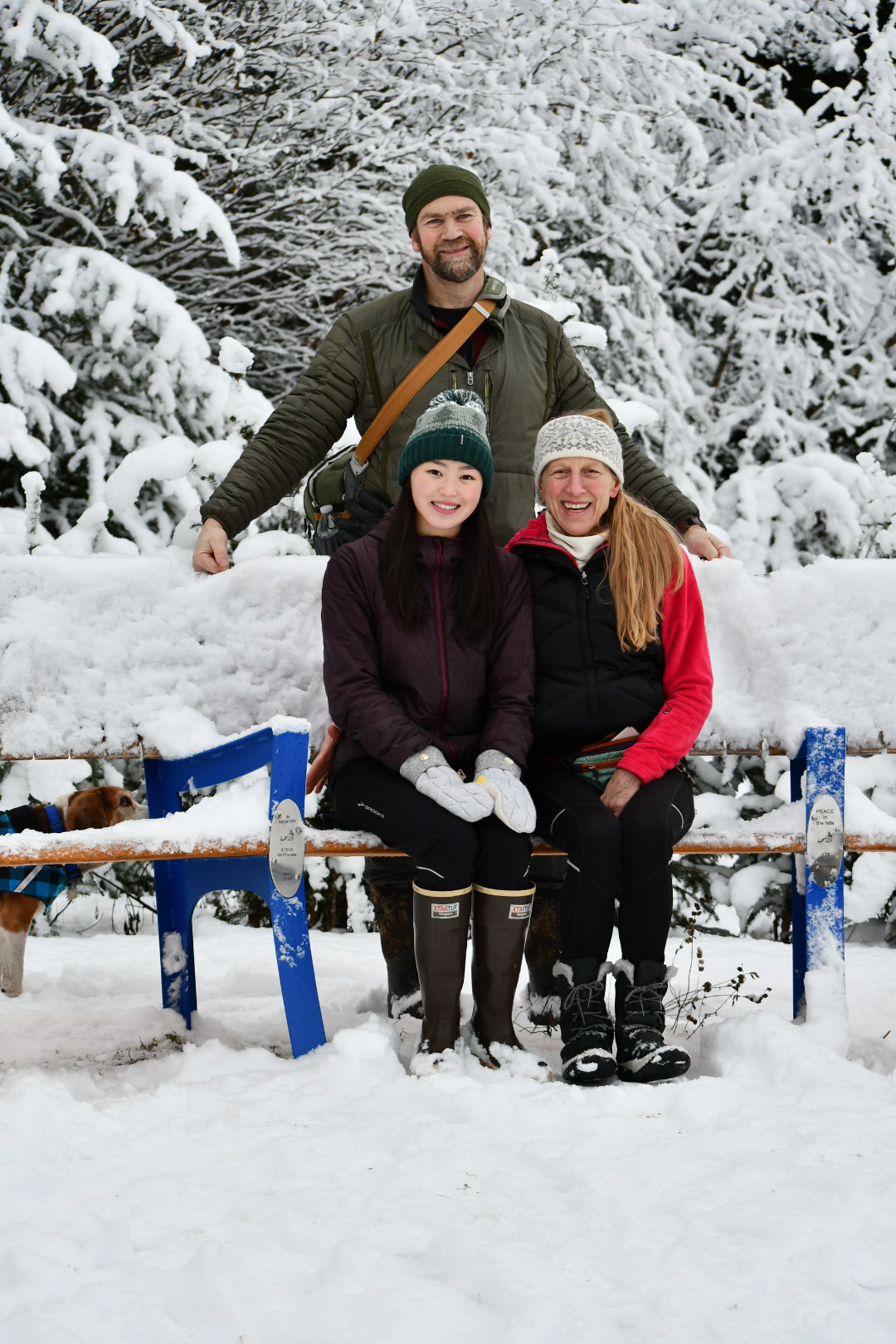 Photo of Pete, Annie, and Sara Hagen sitting on a park bench in the snow.