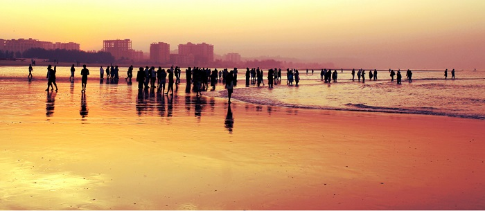 A crowd of people spend time along the water's edge at sunset at sunset.