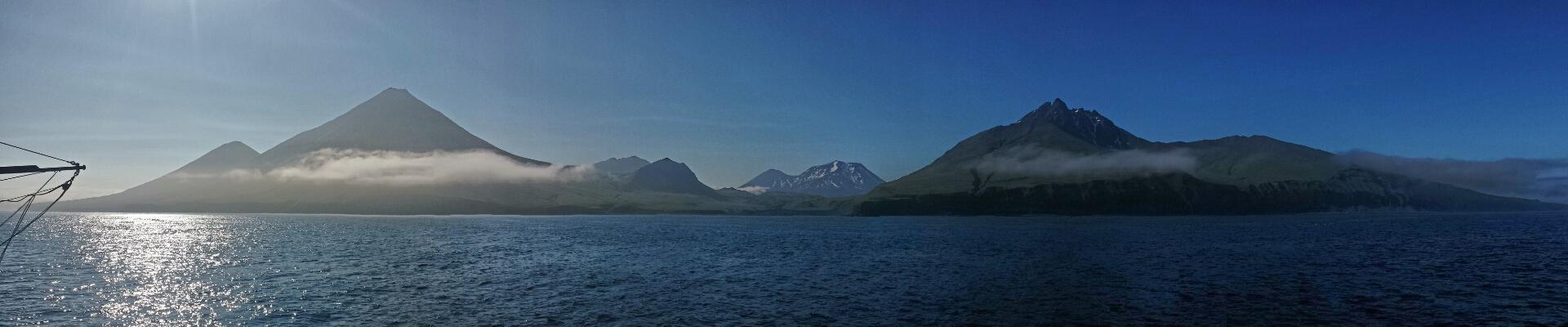 Panoramic off shore photo of Kiska island and volcanic mountains.