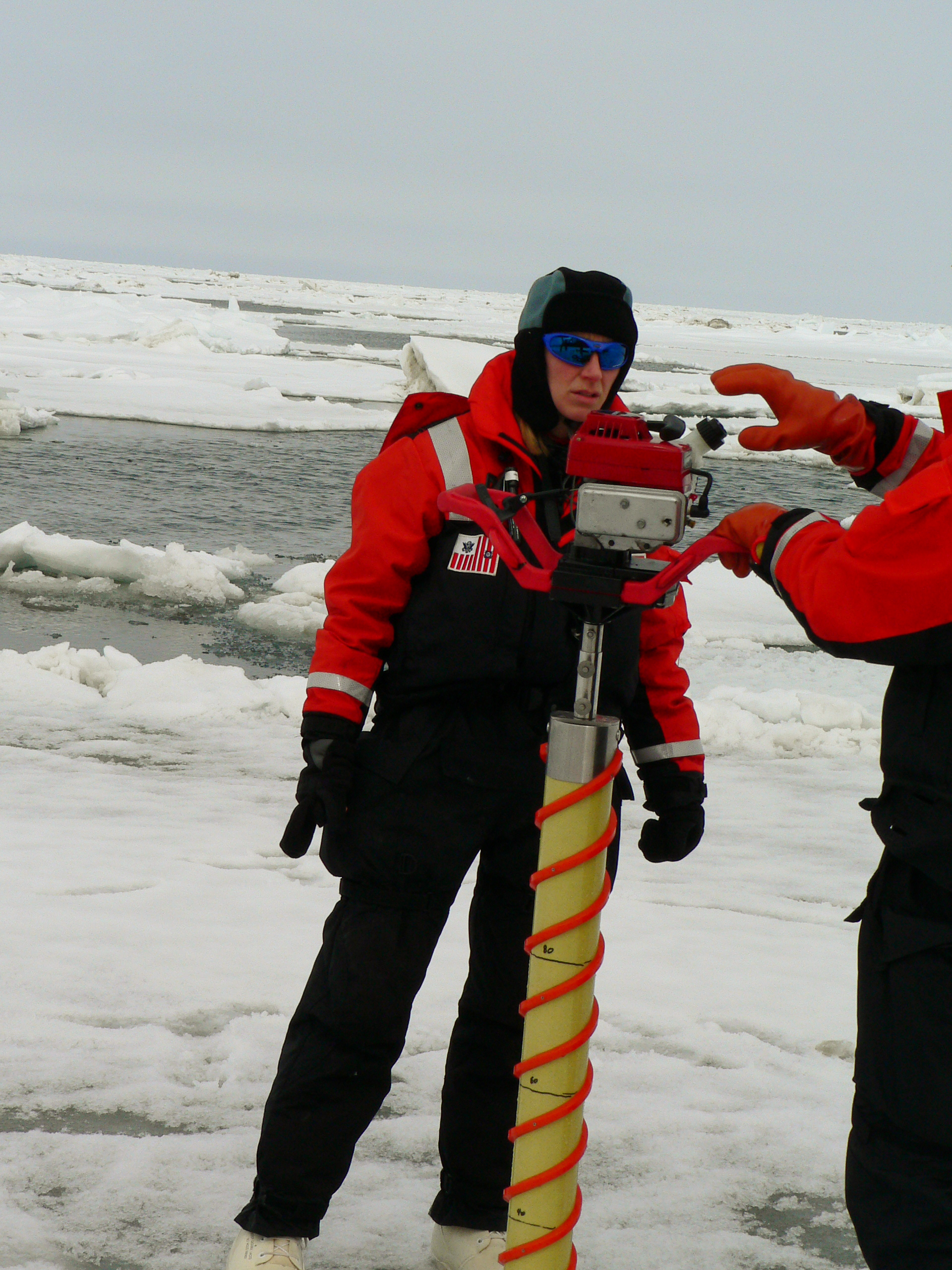 Photo of Ingrid Spies and another researcher using an ice core drilling device on an ice floe.
