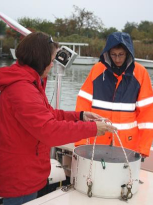 Two women on a boat look at a tray used to sample oyster reefs