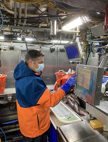 Phil at work station entering data.