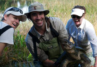 Three people standing in a wetland smile for the camera, with the middle person holding a large turtle