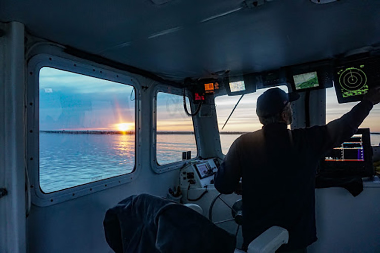 Looking  out the wheelhouse at the sunset to your left.
