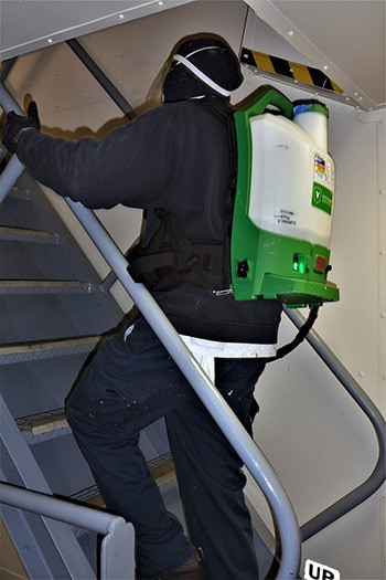 Crewmember spraying railings with disinfectant.