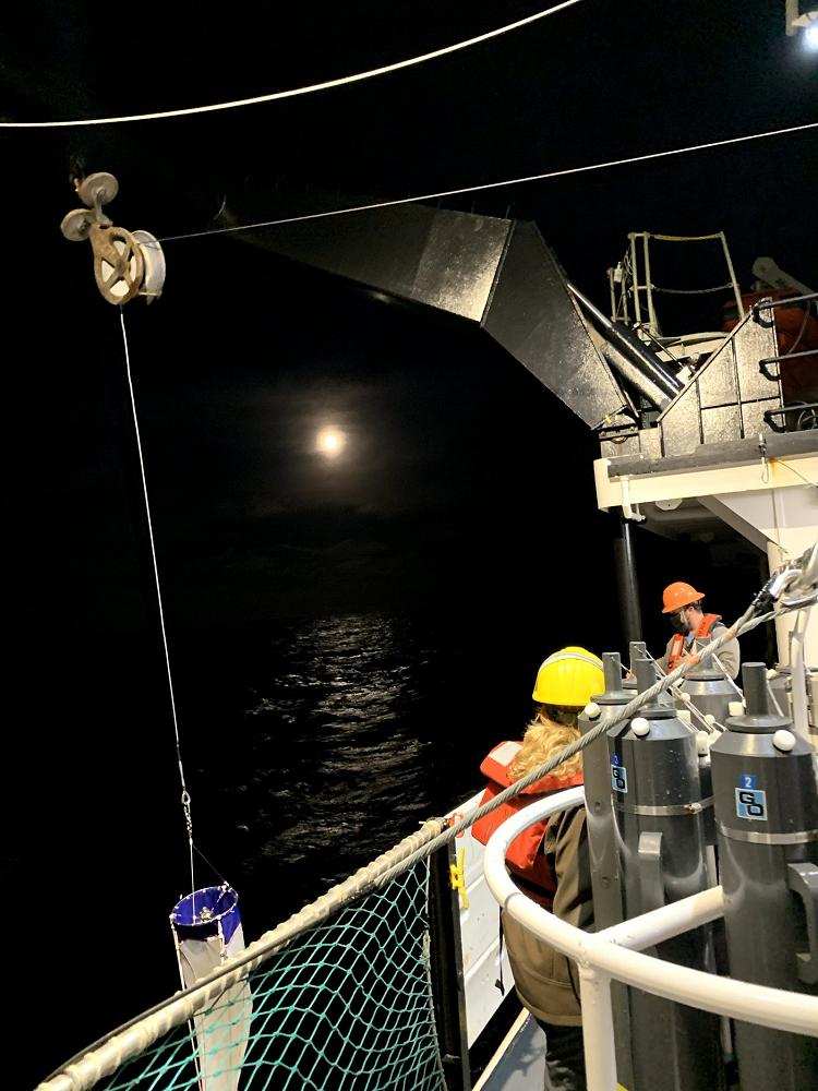 The science night crew deploying a plankton net under the full moon. Photo courtesy of Ashley Hann.