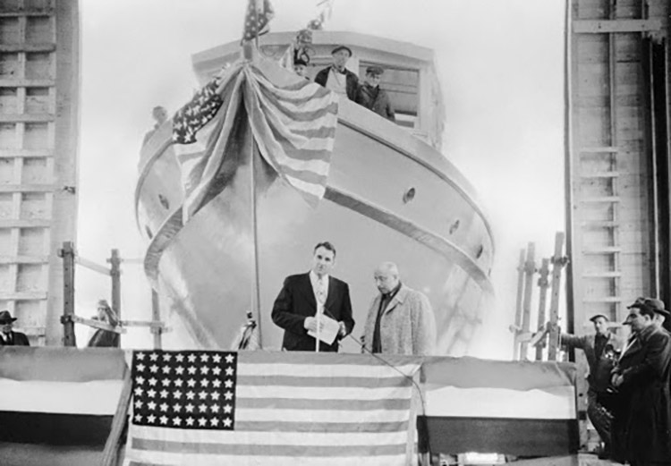 Ship in the background with three men standing on the right side, and an American flag draped over the bow. Two men stand at a podium on a stage in front of the ship. Ronald Clark, the secretary of the shipbuilding company, is speaking at the microphone and presenting the ship to Dr. Victor Loosanoff, who is standing beside him on the right side. An American flag is in front of the stage, and spectators are on both sides.