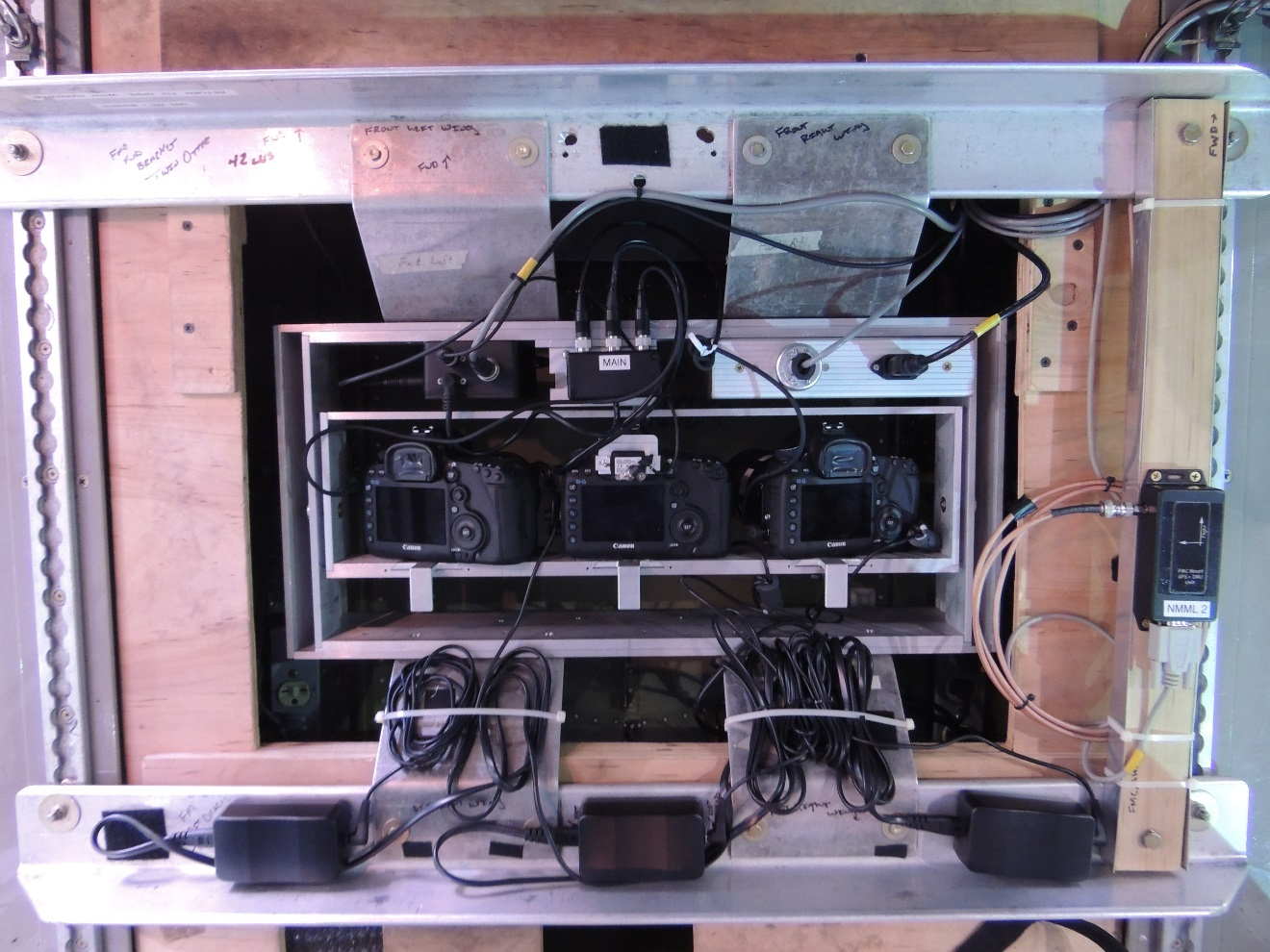 Photo of three cameras and their mounting apparatus in a NOAA Twin Otter aircraft.