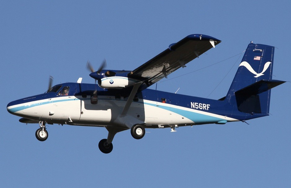 Photo of a NOAA Twin Otter aircraft flying against a clear blue sky.