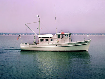 A white wooden ship traverses a calm Long Island Sound on a hazy day, with the coast and coastal homes and buildings just visible in the background. The ship has a blue stripe down the side, a life preserver attached on the outside, and an American flag on the stern.