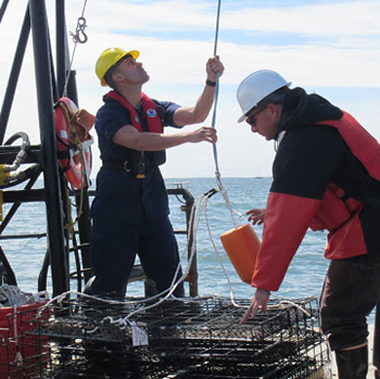 Lieutenant Erick Estela and field technician Dylan Redman rigging lines around an oyster aquaculture cage for deployment from the back deck of the research vessel Victor Loosanoff.