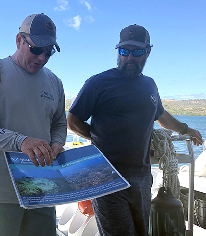 Two people standing on a boat in the water, one of them holding and pointing at a piece of paper with pictures of corals on it