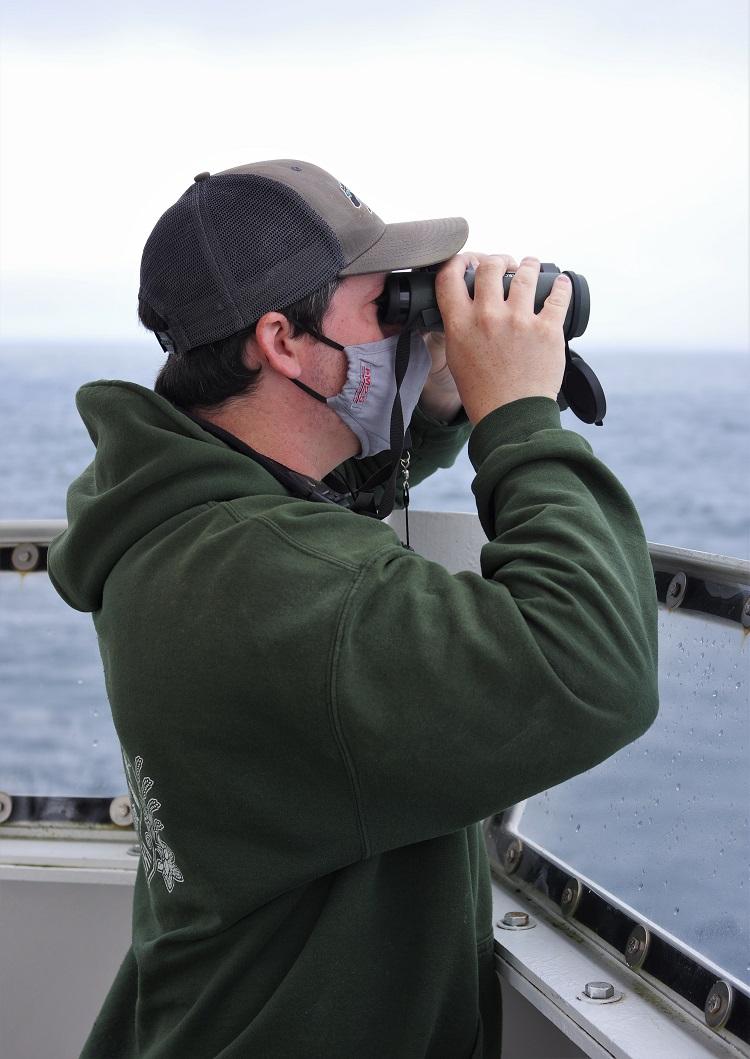"A fisheries biologist scanning the ocean for marine mammals."" Credit: NOAA Fisheries/Steve De Blois"