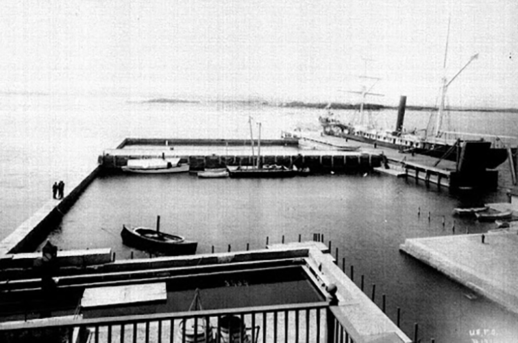 Black and white photo of an enclosed marina. Granite blocks form three sides and a wooden wharf forms the fourth side. The USS Albatross is alongside the wooden wharf, its smokestack and sailless masts clearly visible. An adjacent open pool for holding fish and other live animals is at the lower left. A second wooden wharf spans the refuge a little over halfway from the shore side. A canal connects the refuge to the main lab.