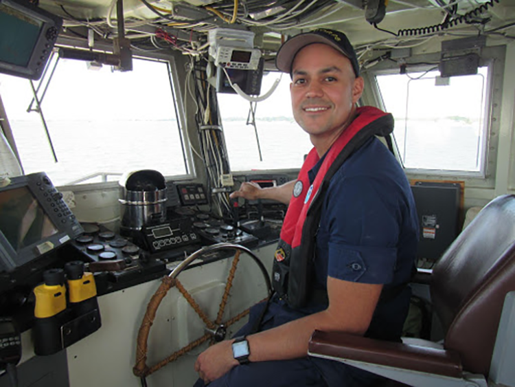 Lieutenant Erick Estela, in the pilothouse, steers the Milford Laboratory's research vessel Victor Loosanoff. Controls are visible on the vessel dashboard.