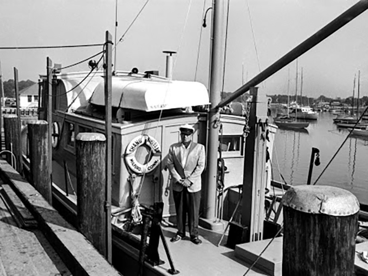 """Victor Loosanoff stands aboard the research vessel Shang Wheeler at the dock. He's wearing a captain's hat and a blazer, and a life preserver is in the background attached to the ship with the words """"Shang Wheeler, Milford, Conn"""". Boats on moorings and Milford Harbor are visible in the background."""