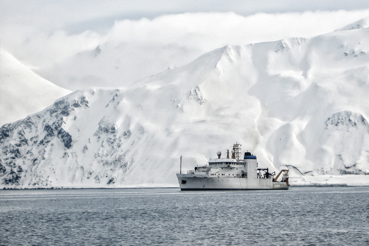 Photo of a NOAA survey vessel off the coast of Alaska with steep snow covered mountains rising from the waterline.
