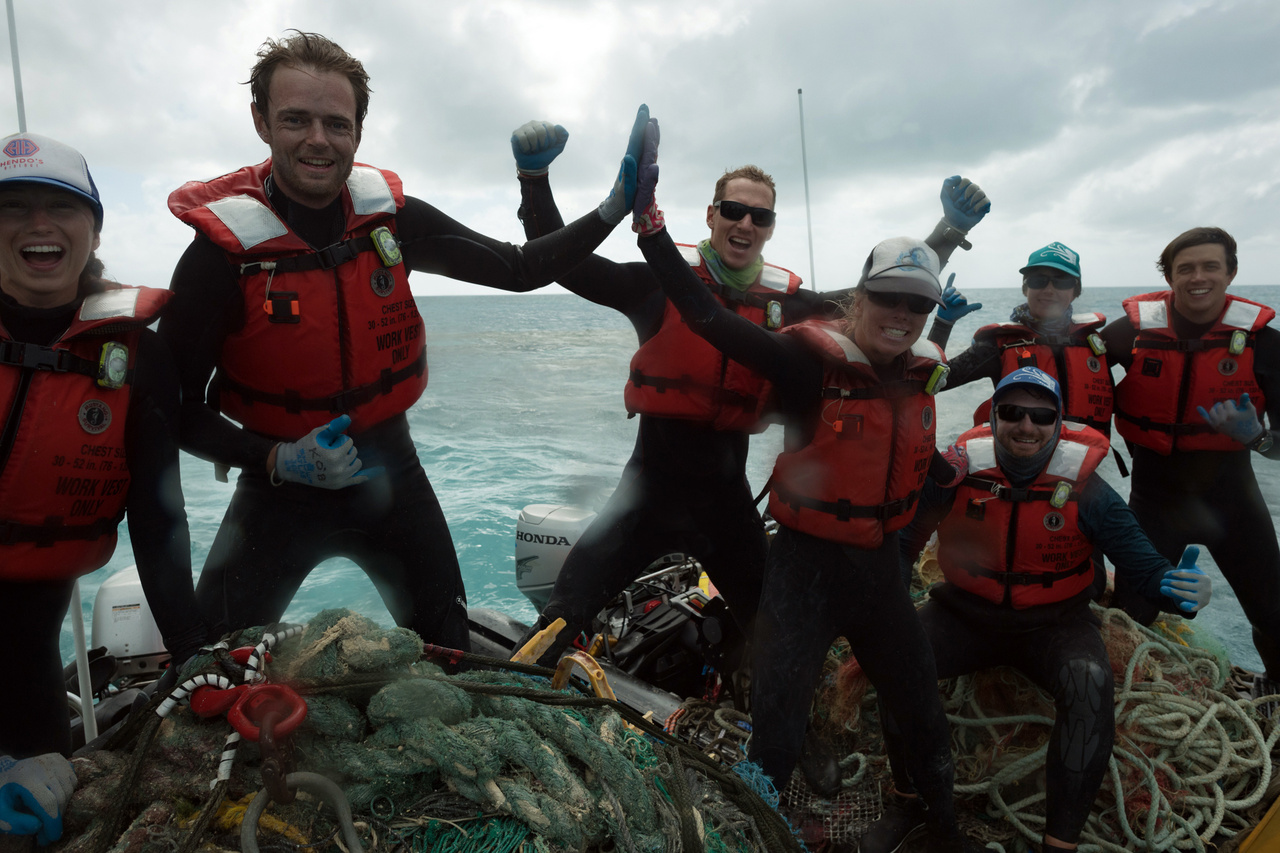 The team celebrates successfully removing another net from the reef