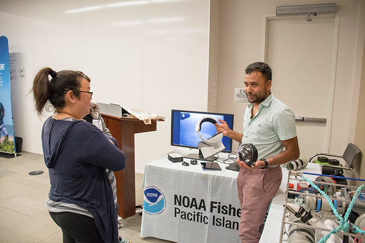 NOAA staff presents equipment used in fisheries research to teacher workshop participant.