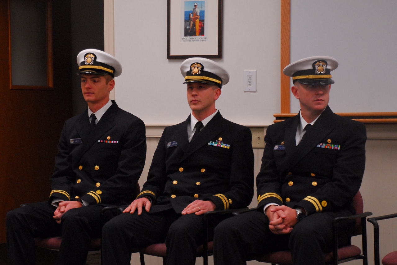 Three seated NOAA Corps officers await start of the change of command ceremony
