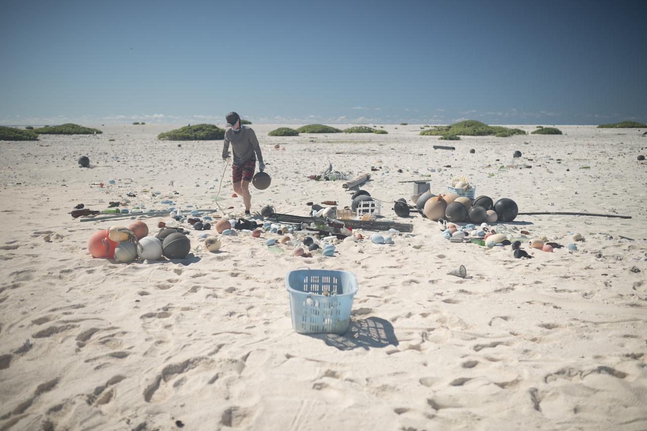 Marine debris technician cleans up debris along the beach