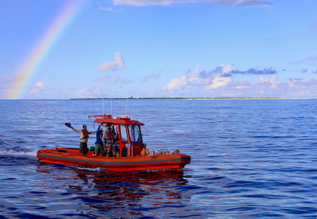 One of the small boats returns to the ship under a rainbow after collecting water samples and deploying instruments around Kure Atoll.  <i>Photo: NOAA Fisheries/James Morioka. </i>
