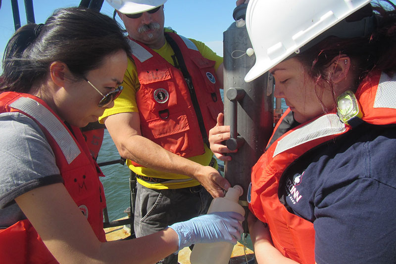 Scientists on the deck of a research vessel pouring seawater sample into a plastic bottle.