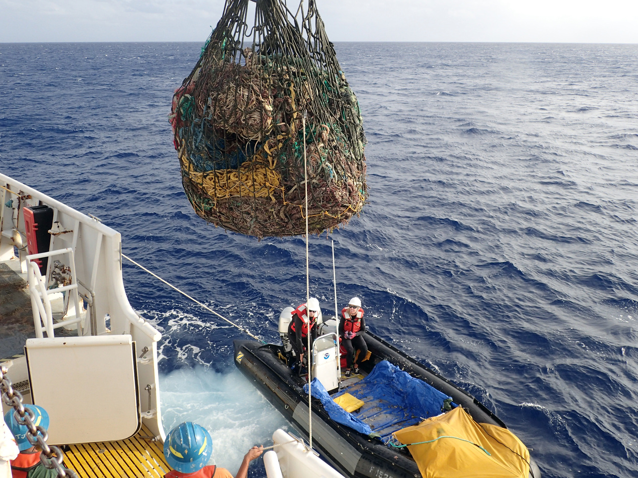 A metric ton of net is lifted from the small boat to the NOAA Ship by crane
