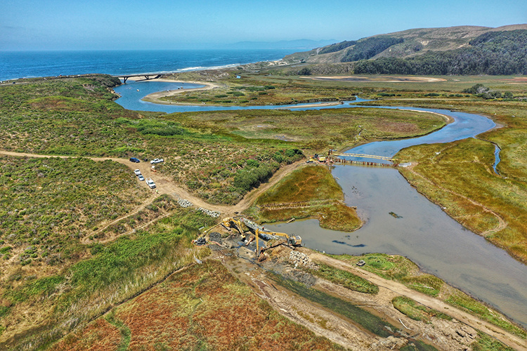 Aerial view of a marsh with construction equipment, with the ocean in the background