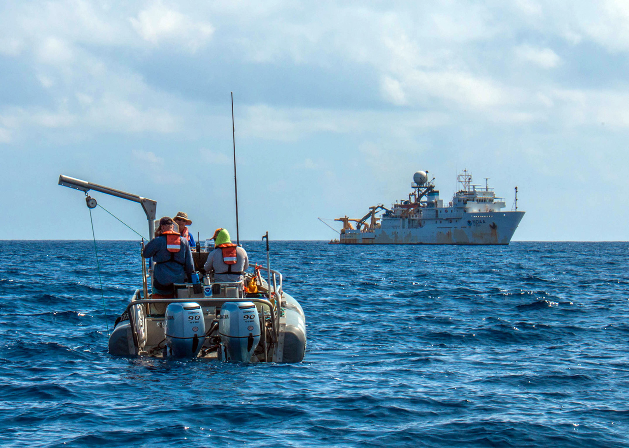 Researchers deploy the MOUSS underwater camera system from a small boat.