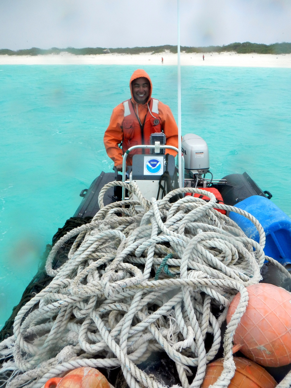 NOAA Coral Reef Ecosystem Program Marine Debris team lead, James Marioka, navigates one of the inflatable boats full of derelict fishing nets away from Kure Atoll.  The abandoned gear will be loaded onto NOAA Ship Hi'ialakai for transport back to Honolulu along with the rest of the debris collected during the mission. Photo: NOAA Fisheries