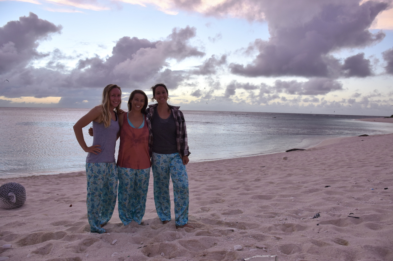 Laysan field biologists stand on beach at sunset.