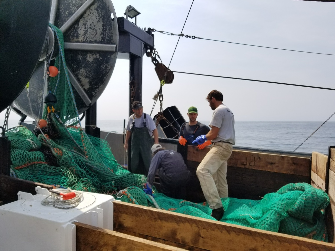 Crew on deck, green nets and winch visible.