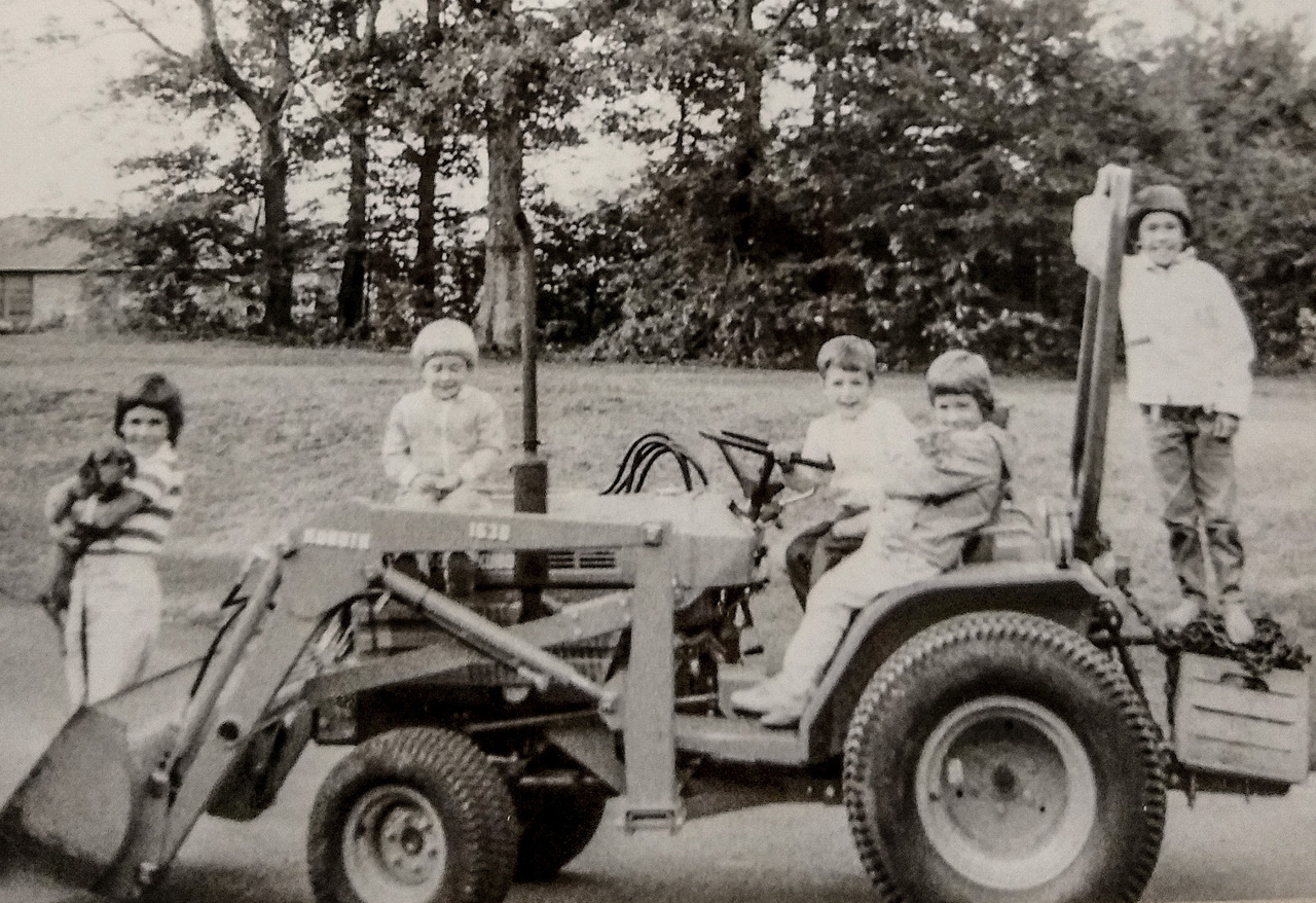 black and white picture of family posing around a tractor