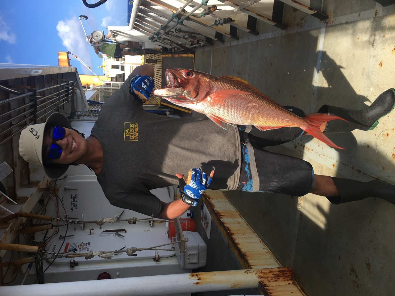 Max holds up one of the beautiful and vibrantly colored lehi that he caught to study deepwater fishes.