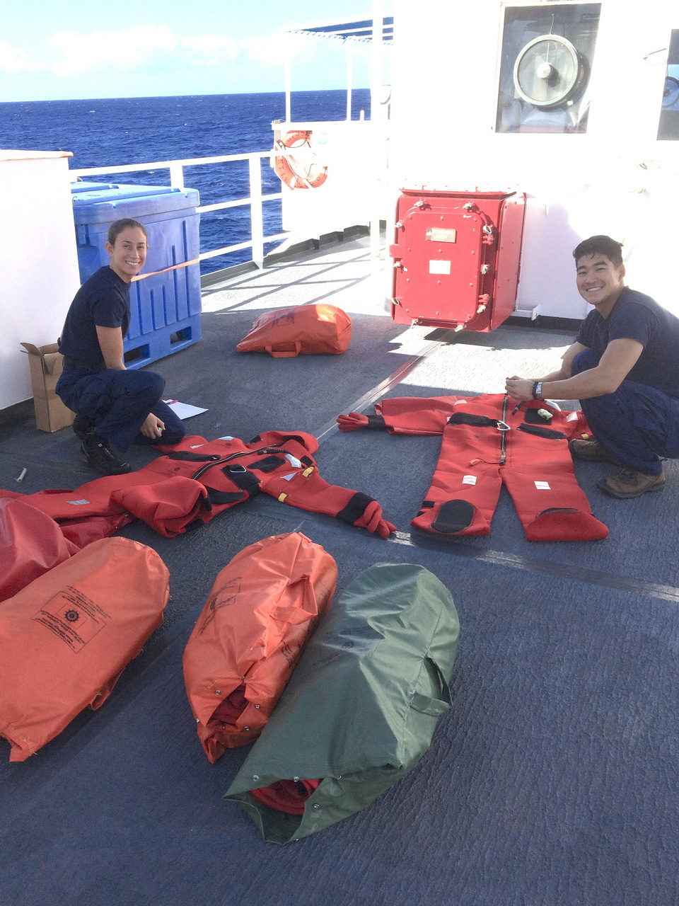 """Ensigns Moore and Park check the condition of survival suits (a.k.a. """"gumby suits"""") before a weekly abandon ship drill. Photo: NOAA Fisheries/Suzanne Yin."""