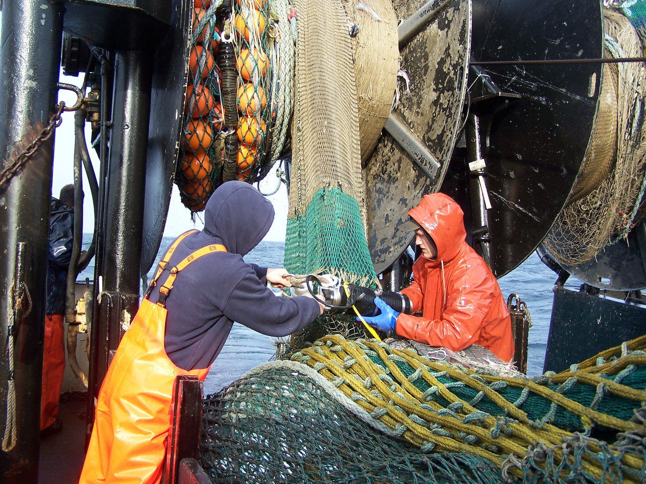 men attaching data recorder to fishing net
