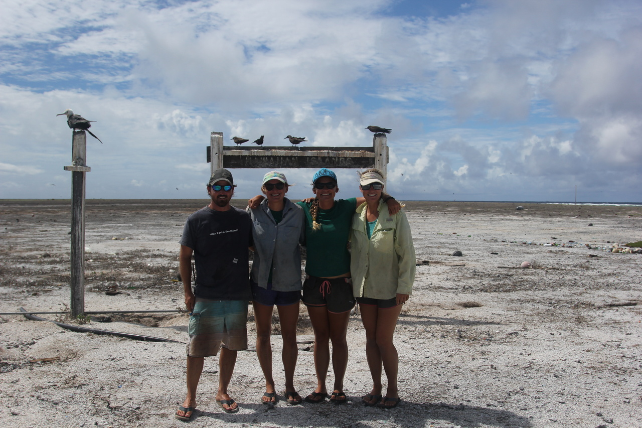 Pearl and Hermes field camp biologists stand in front of a sign for the Hawaiian Islands.