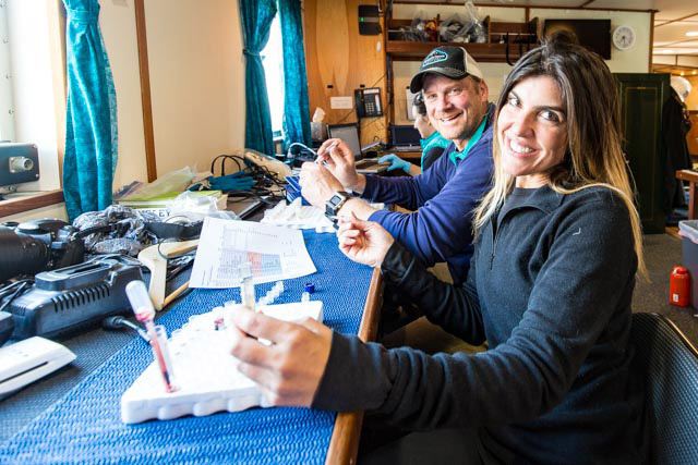 """Jennifer Rego (SeaWorld, San Diego) and John Jansen (AFSC, NOAA) take a break from pipetting harbor seal blood aliquots inside the """"lab"""" of the R/V Norseman., Photo by Josh London"""