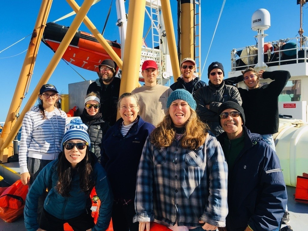 men and women of a scientific crew pose on the ship's deck