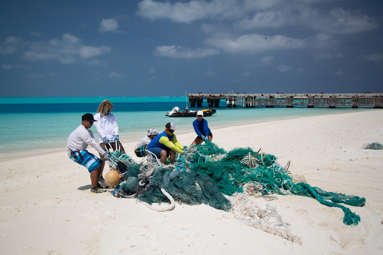 The team continued removing debris from the shorelines of Eastern Island on April 16, 2016. The team members hauled a large net conglomerate into a small boat. Photo: NOAA Fisheries/Ryan Tabata