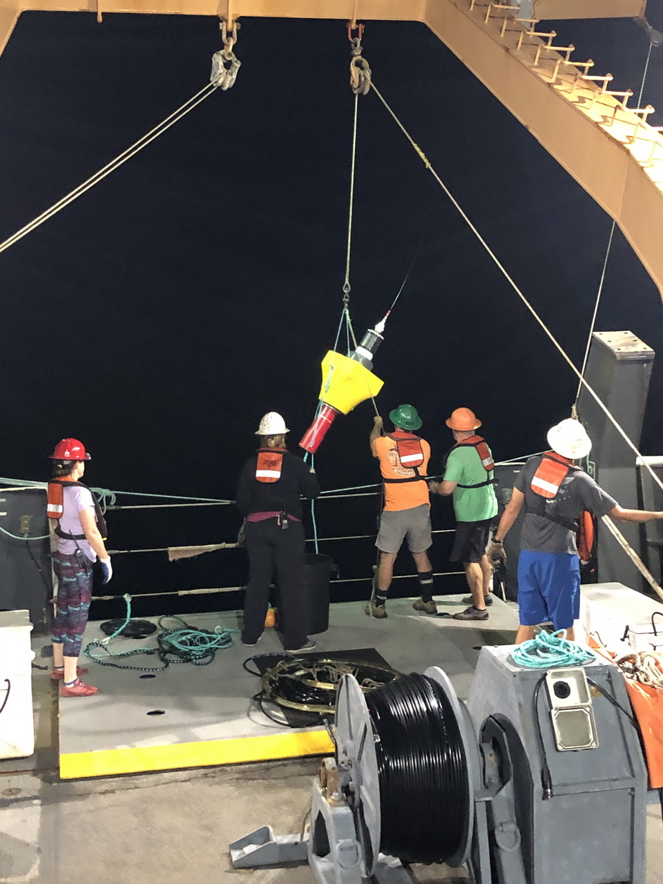 The acoustics and deck crews deploy a DASBR+ that was modified with help from the PIFSC Science Operations fabrication team.  This DASBR includes lights and an AIS system for improved nighttime retrieval. Photo: NOAA Fisheries.
