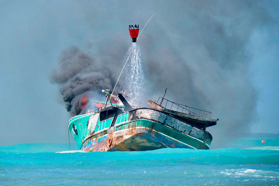 A Fire Department helicopter pours water onto Pacific Paradise to put out a sudden fire.