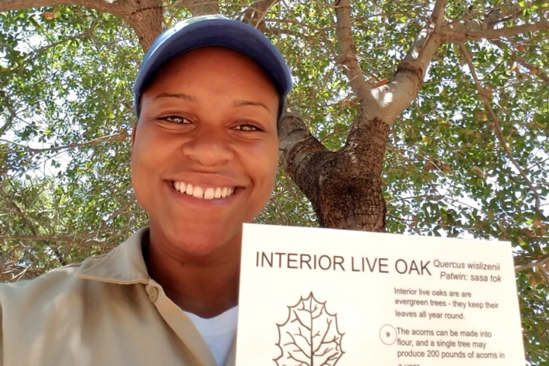 Fish Migration Vet Corps Xavia Jackson shows off educational materials she developed - an info card on Live Oak trees and their benefits to river habitats.