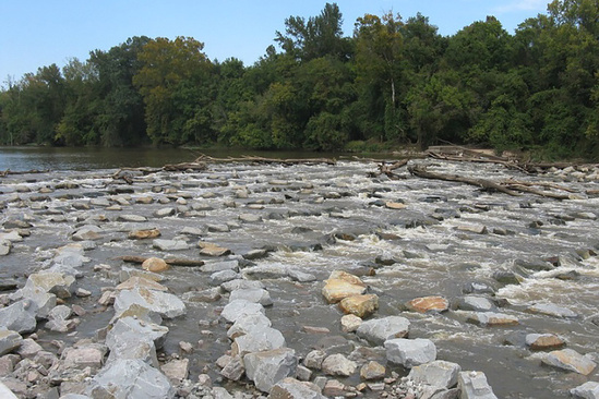 Gently sloping ridges of rocks line the bed of a river