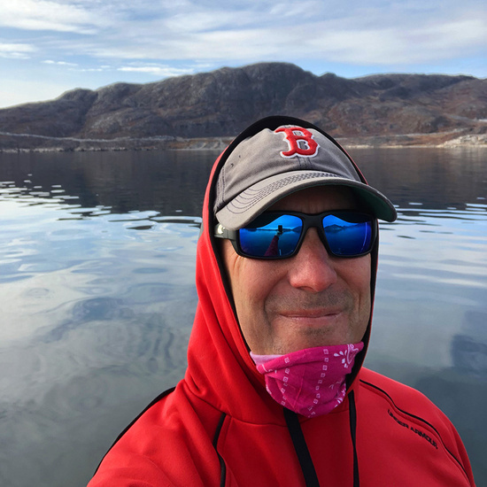 Bundled up in a red sweatshirt, Tim Sheehan takes a selfie in the Qaqortoq fjord, Greenland.
