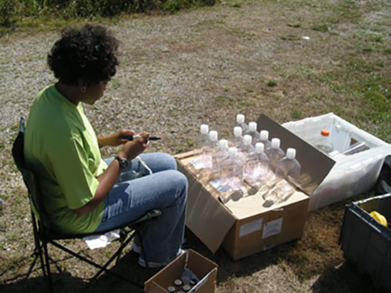 April Croxton working on samples at a creek