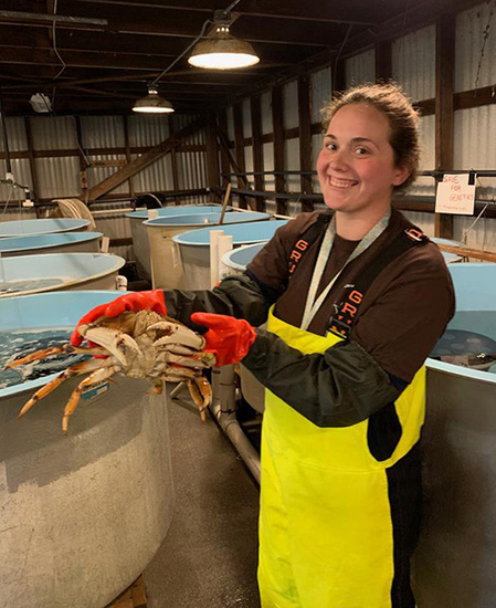 Kate Rovinski holds a Dungeness crab in a research facility