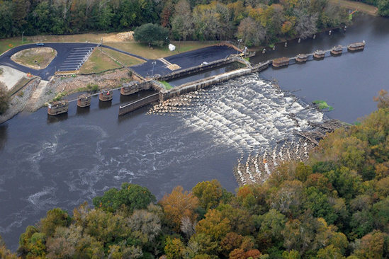 An aerial view of a river flowing over a lock and dam structure